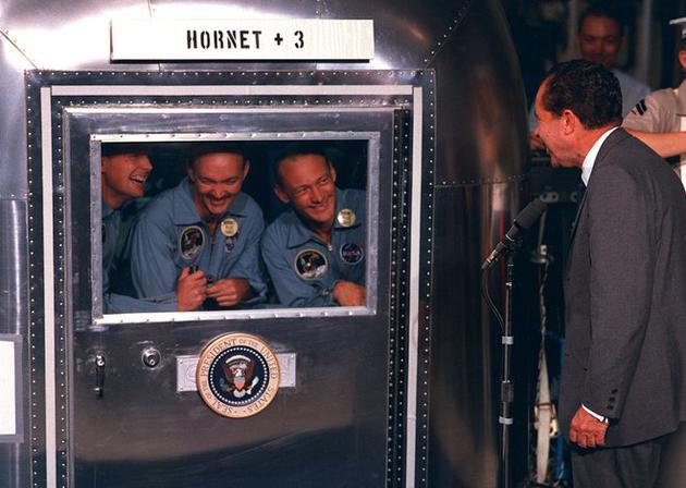 图为尼克松总统正在欢迎阿波罗11号的宇航员们返回地球。宇航员需进行为期21天的隔离,以确保未从月球带回任何污染物。
